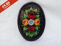 Oval Pottery Wall Plaque, black background,  hand-painted with traditional canal rose design.